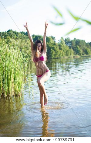 Pretty young lady in pink swimwear jumping with raised arms
