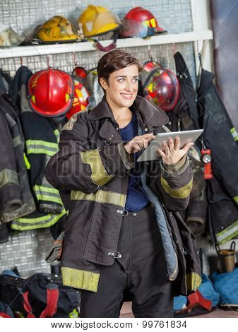 Smiling firewoman looking away while using digital tablet at fire station
