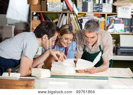 Male and female workers analyzing papers together in factory