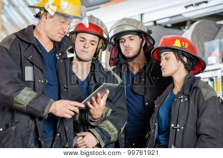 Team of firefighters using tablet computer at fire station