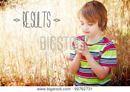 The word results against praying little boy in the park