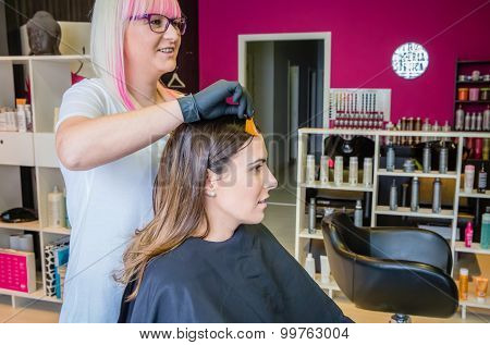 Hairdresser showing hair dye sample to young woman