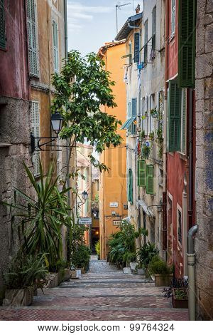 VILLEFRANCHE-SUR-MER, FRANCE - OCTOBER 4, 2014: Narrow street with colorful old buildings leads down to Mediterranean sea in medieval town Villefranche-sur-Mer on French Riviera, France.