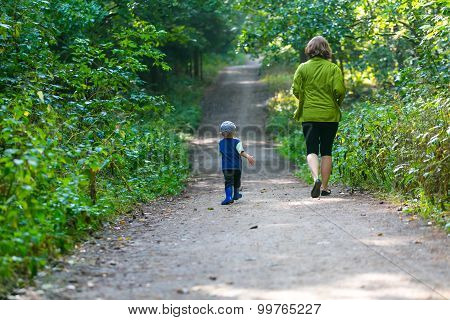 Little Boy And Mother Running And Playing In Forest At Summer.