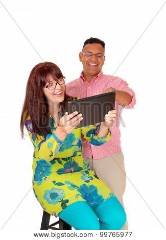 A Middle Age Couple Having Fun With The Tablet.