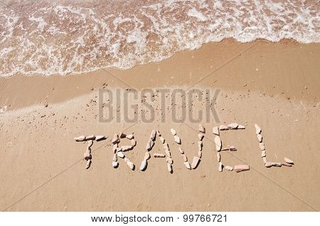 travel written on sandy beach near sea