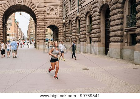 Young attractive girl running near the Royal palace in Gamla Sta