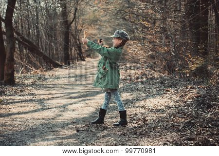 little girl playing with a slingshot in the woods, photo in vintage style