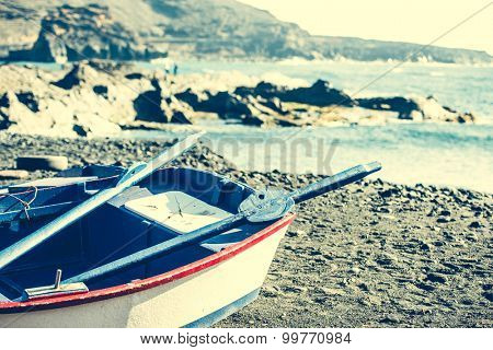boat on a sandy shore on rocky coastline background
