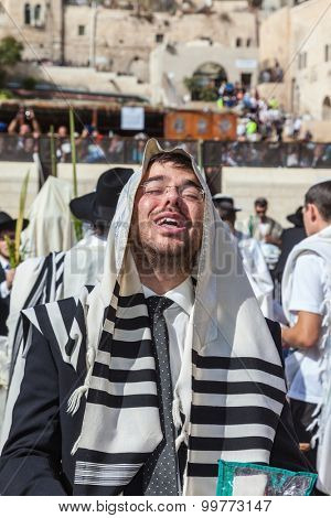 JERUSALEM, ISRAEL - OCTOBER 12, 2014: The area in front of Western Wall of  Temple filled with people.   Young boy in tallit praying. Morning autumn Sukkot