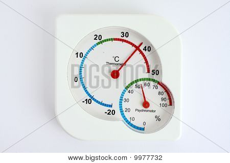 Old thermometer and hygrometer on white paper.