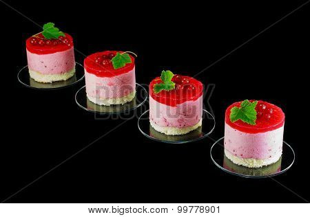 Four small redcurrant cakes decorated with berries