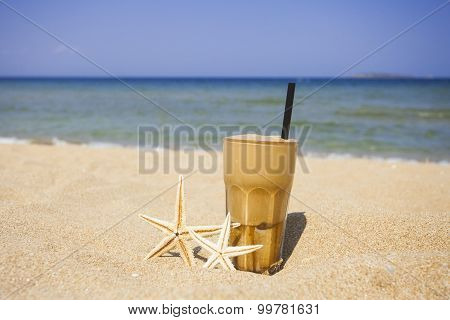Iced coffee on a sandy beach background