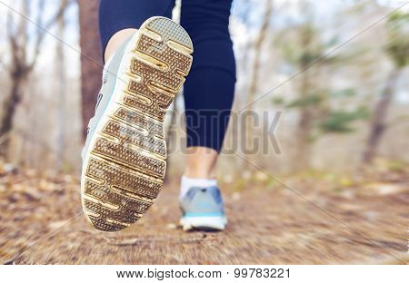 Woman Jogging In The Forest In The Fall