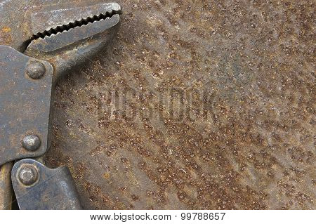 Old Pipe Wrench On Rusty Metal Background