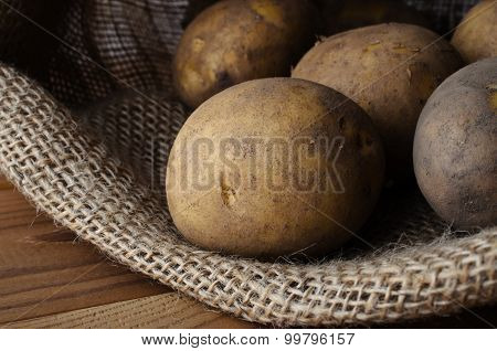 Raw Potatoes In Opened Sack On Wood Table