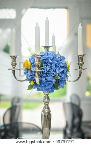 Antique candlestick with blue flowers wedding bouquet. Wedding candlestick with flowers decoration