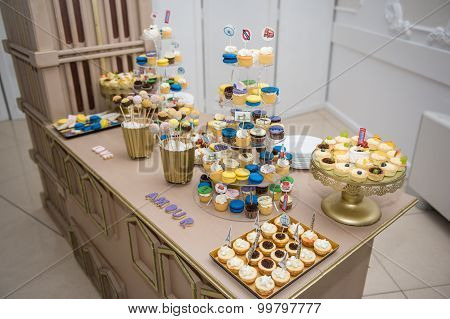Wedding decoration with pastel colored cupcakes, meringues, muffins and macarons. Elegant and luxuri