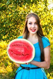 stock photo of cucurbitaceous  - Beautiful young woman holding half of juicy watermelon - JPG