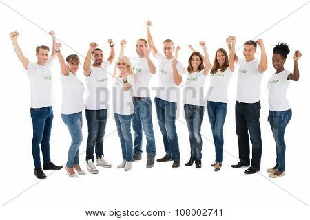 Confident Volunteers With Arms Raised Standing In Row