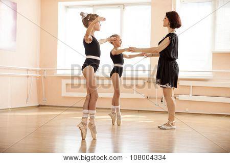 Ballet teacher helping young girls to dance en pointe.