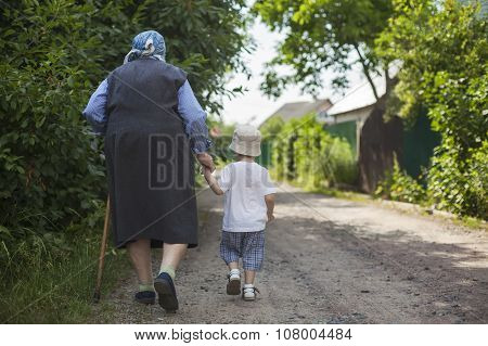 Great grandmother and toddler boy walking down street.
