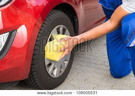 Worker Cleaning Car Wheel With Sponge