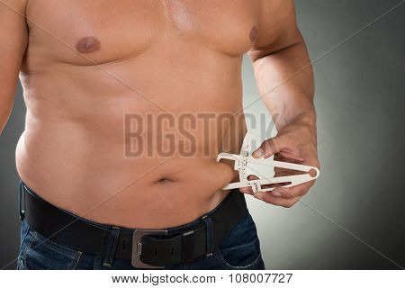 Shirtless Man Measuring Stomach Fat With Caliper