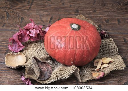Orange Pumpkin And Old Dry Leaves Lying On Vintage Homespun Canvas