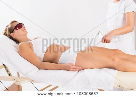 Woman Receiving Laser Treatment On Leg