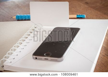 Smart Phone And Business Card On Opened Notebook