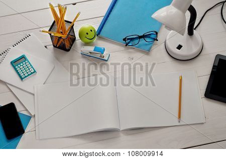 Designer's Desk With Tools And Open Album With Blank Pages