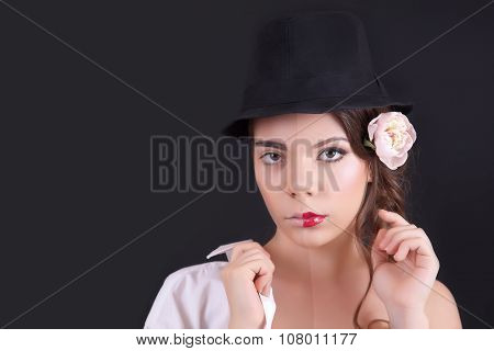 Portrait Of The Woman With A Theatrical Makeup On Black Background