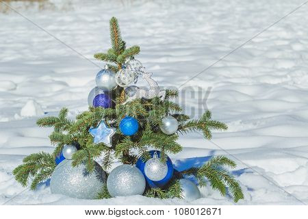 Natural conifer snowy tree decorated with Christmas ornaments and baubles