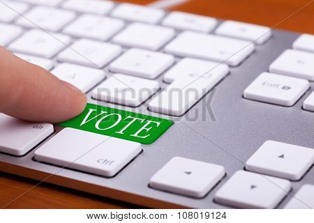 Finger Pressing On Vote Green Button On Keyboard