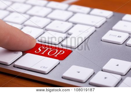 Finger Pushing Red Stop Button On Modern Keyboard