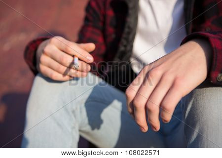 Close Up Of Teenage Boy Smoking Cigarette Outdoors