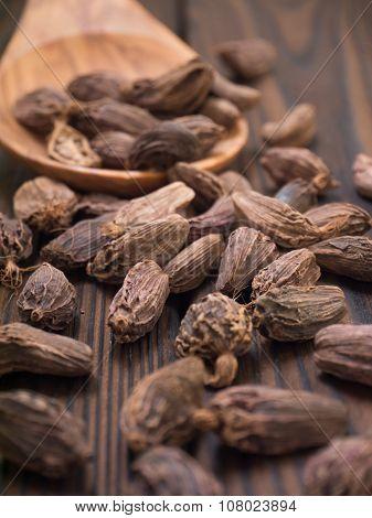 Black Cardamom Pods In The Wooden Spoon
