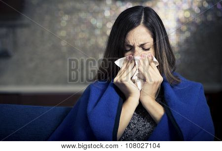 Sick young woman is coughing and blowing.