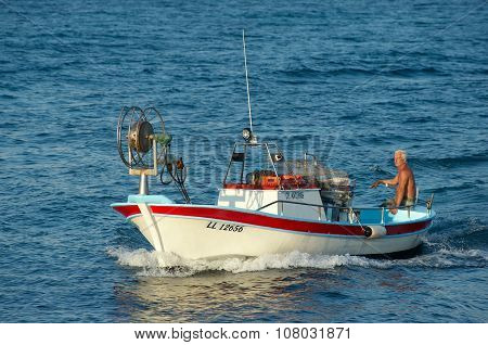 Fisherman swims on his fishing boat in the sea