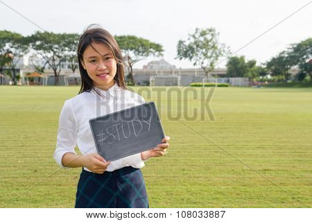 Beautiful and lovely female student hold a blackboard study on the grass field
