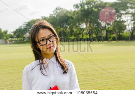 Portrait of young and happy female student on the grass field