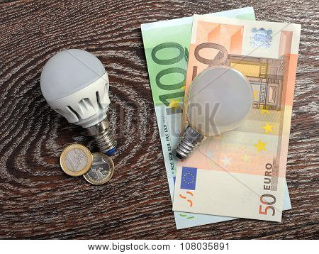 LED bulb and incandescent lamp at euro bills