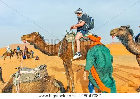 MERZOUGA, MOROCCO, APRIL 13, 2015: Local man in traditional attire helps a tourist to prepare to camel trip on sand dunes of Erg Chebbi