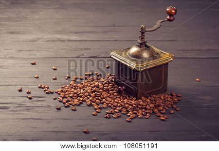 Old vintage bronze coffee mill on spilled roasted hot beans. Illustration