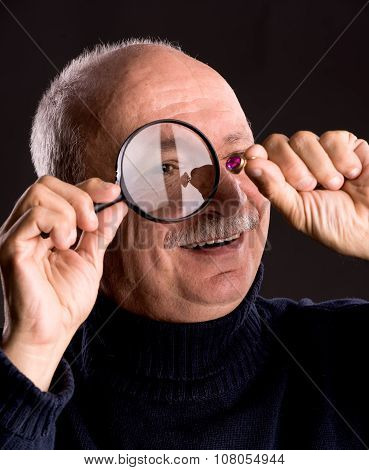 Senior Jeweler Looking At Jewelry Through Magnifying Glass