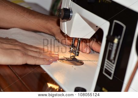 closeup of a young caucasian man sewing a beige fabric with a sewing machine