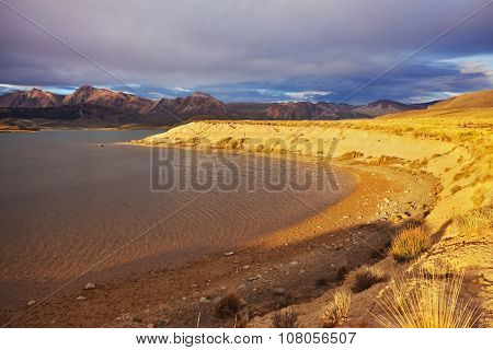 The glassy surface of a mountain lake. The lake reflects the sunset