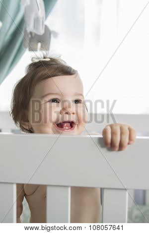Infant baby resting and playing in her little baby bed