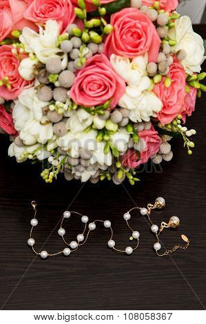 Vintage wedding bouquet with gold chain arranged in form of word Love